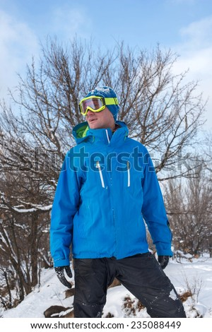 Joyful snowboarder looking at the sun - stock photo
