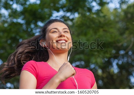 Joyful sporty woman jogging in a park listening to music - stock photo