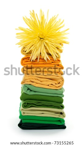 Joyful spring laundry. Flower on top of green and yellow folded clothes.