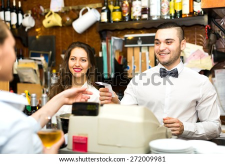 Joyful staff working in a bar: female bartender is smiling, male barista is handing over a check to a waiter - stock photo