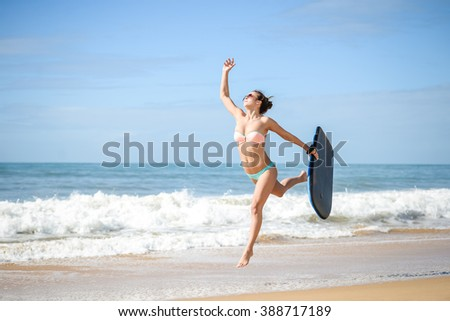 Joyful surfer girl happy cheerful running surfing at ocean beach water. Female bikini heading for waves with surfboard having fun on vacation