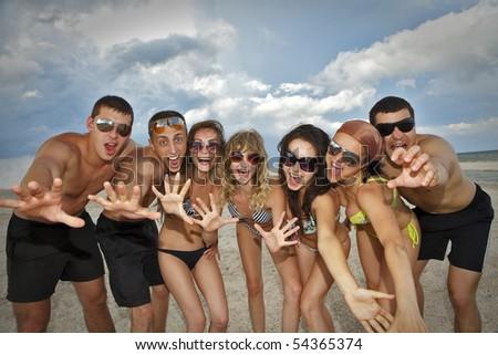 Joyful team of friends having fun at the beach - stock photo