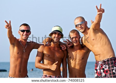 Joyful team of friends having fun at the beach - stock photo