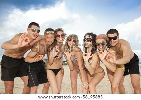 Joyful team of friends having fun at the beach and showing okay sign - stock photo