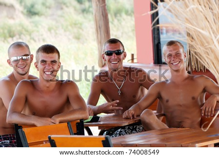 Joyful team of friends having fun at the beach in cafe - stock photo