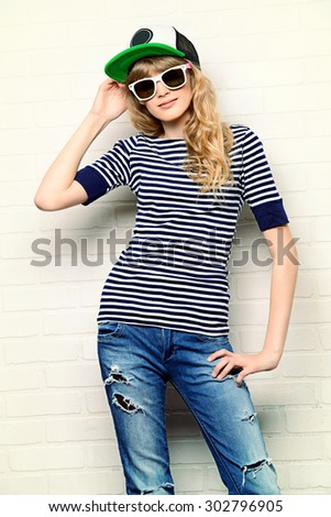 Joyful teen girl in casual clothes and sunglasses posing by a brick wall. Active lifestyle. Youth fashion. Studio shot.  - stock photo
