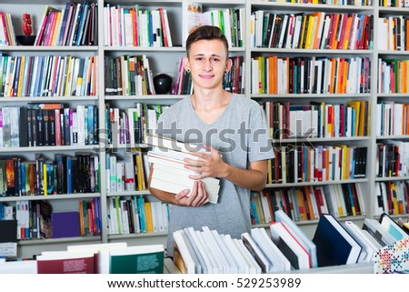 joyful teenage boy having book pile in hands in book shop