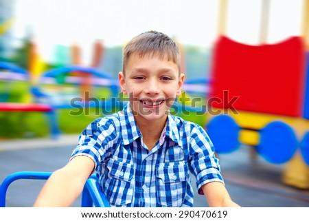joyful teenage boy having fun on roundabout, playground - stock photo