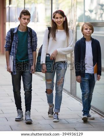 Joyful teenage students going to college through city street - stock photo