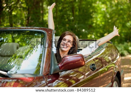 Joyful Teenager Female Driver Arm Out in Convertible car - stock photo