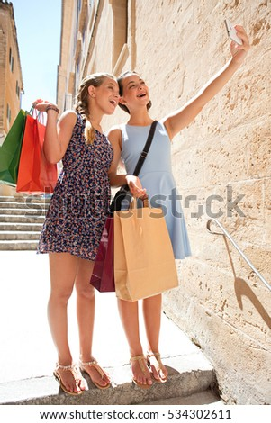 Joyful teenagers girls friends in a picturesque stone destination city holding a mobile phone, taking selfies photos together, smiling outdoors. Adolescents with shopping bags using technology.