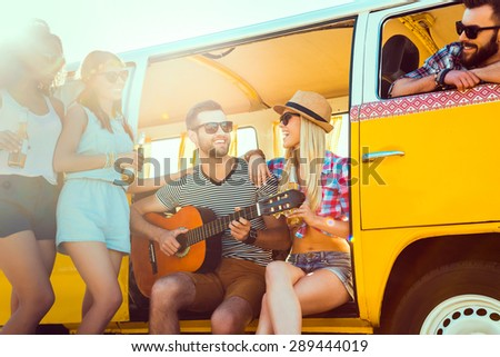 Joyful time with close friends. Group of young cheerful people enjoying time together near their retro minivan  - stock photo