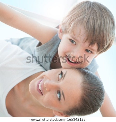 Joyful toddler on back of his mother - family enjoying moments of happiness - stock photo