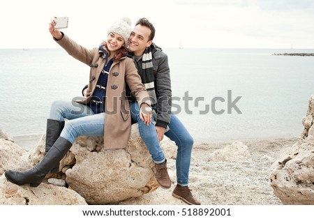 Joyful tourist couple sitting on rocky beach, posing with heads together taking selfies on a winter holiday, smiling having fun. Young couple using smart phone technology, travel lifestyle, outdoors.