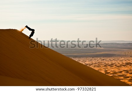 Joyful tourist jumping flip from sand dune - stock photo