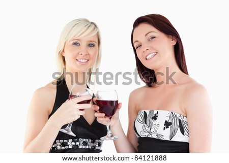 Joyful well-dressed women toasting with red wine in a studio