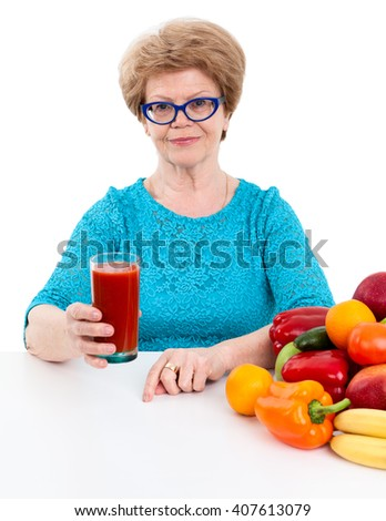 Joyful woman at the age offering fresh tomato juice in her hand, isolated on white background - stock photo