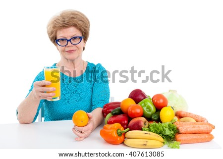 Joyful woman at the age suggests fresh orange juice in her hand, isolated on white background - stock photo