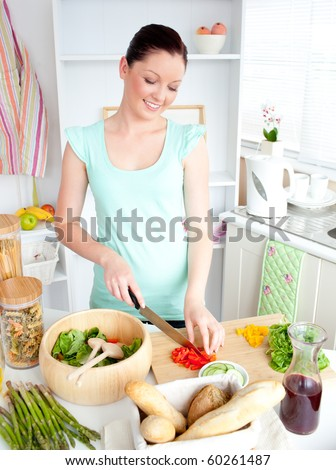 Joyful woman cutting pepper at home in the kitchen - stock photo