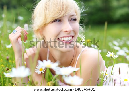 Joyful woman enjoying summer lying in a meadow of white daisies looking back with a smile, closeup facial portrait with shallow depth of field - stock photo