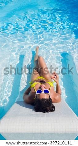 Joyful woman having fun sunbathing and drinking cocktail in hotel resort spa pool on summer vacation. - stock photo