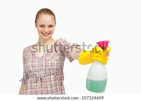 Joyful woman holding a spray bottle while smiling against white background - stock photo