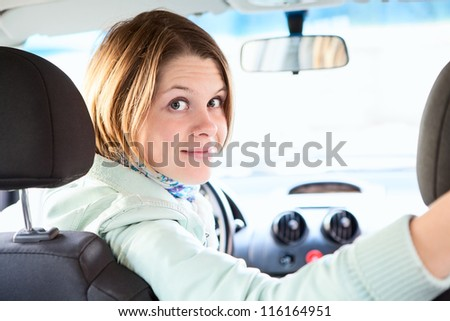 Joyful woman inside of car looking back from driver seat - stock photo