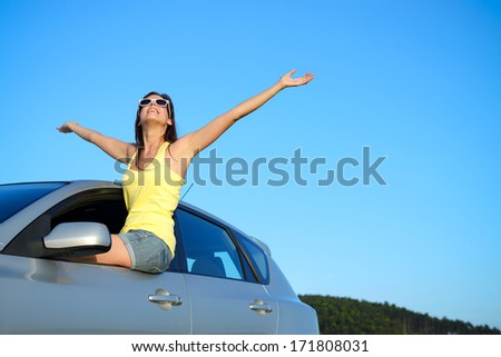 Joyful woman on car summer roadtrip. Blissful girl having fun on travel. - stock photo