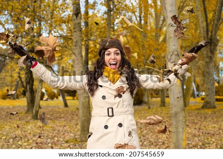 Joyful woman playing with autumn leaves and having fun in city park. Successful caucasian brunette enjoying fall season and laughing. - stock photo