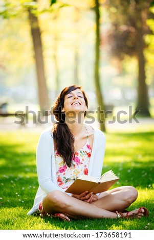 Joyful woman reading fun book sitting on grass in park. - stock photo