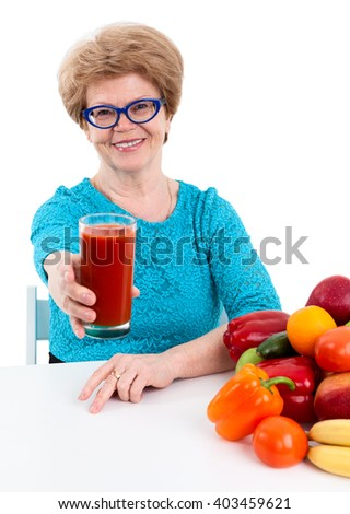 Joyful woman retirement age stretching hand with glass of tomato juice, isolated on white background - stock photo