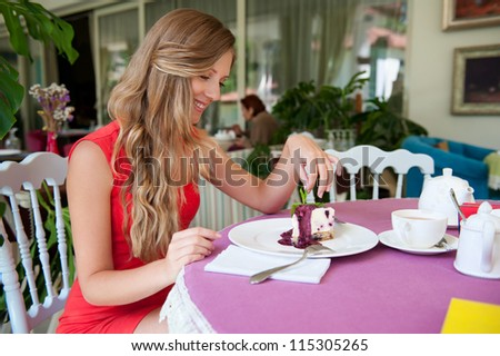 joyful woman sitting in the cafe and looking at cake - stock photo