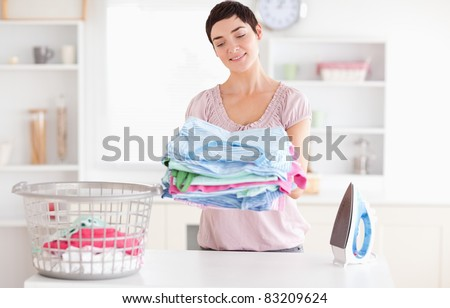 Joyful Woman with a pile of clothes in a utility room - stock photo