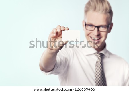 Joyful young businessman holding white blank business card with space for text, isolated. - stock photo
