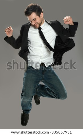 Joyful young businessman jumping isolated over gray background - stock photo