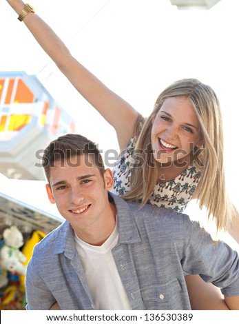 Joyful young couple being playful at an amusement park, with young man carrying his girlfriend on his back near a ferris wheel. - stock photo