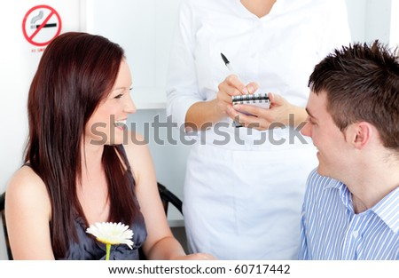 Joyful young couple dining at the restaurant with waiter taking order - stock photo
