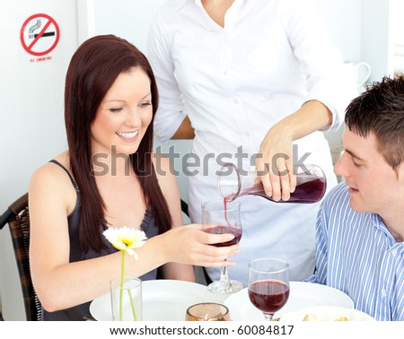 Joyful young couple having dinner at the restaurant with waiter serving them wine - stock photo