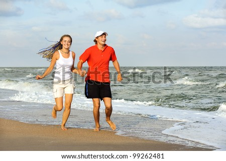 Joyful young couple running on sea shore. - stock photo
