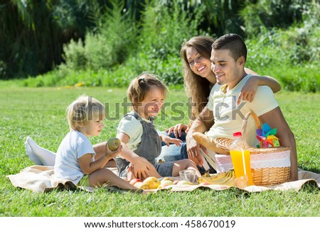 Joyful young family of four on picnic in park at summer day. Focus on girl