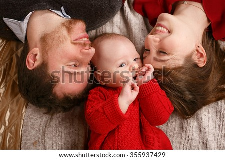 Joyful young family with a baby lying on the bed and smiling happily. The joy of parenthood. - stock photo