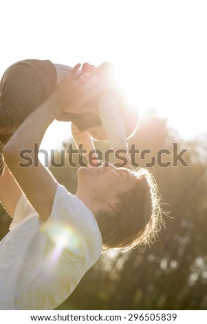 Joyful young father lifting and kissing his baby boy in front of the warm glow of a morning sunburst. - stock photo