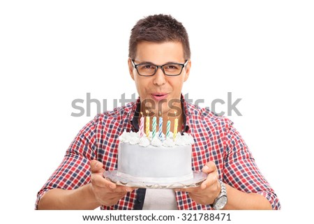 Joyful young man blowing candles on a birthday cake and looking at the camera isolated on white background - stock photo