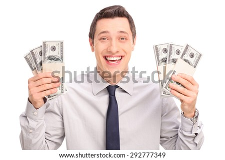 Joyful young man holding six stacks of money and looking at the camera isolated on white background - stock photo
