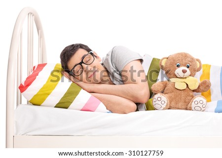 Joyful young man sleeping in a bed with a teddy bear isolated on white background - stock photo