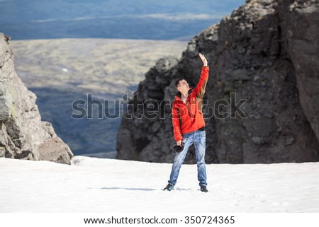 Joyful young man standing on the mountain pass glacier with hand up to the sky and enjoying the sun