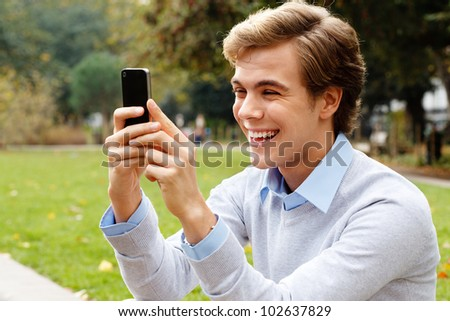 Joyful young man video messaging outdoors - stock photo