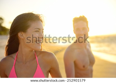 Joyful young mixed race couple on beach sunset enjoying summer vacation holiday travel. Beautiful smiling Asian woman, young pretty Caucasian male. Hawaii. - stock photo