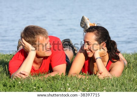 Joyful young pair is overlapping shore of the lake - stock photo