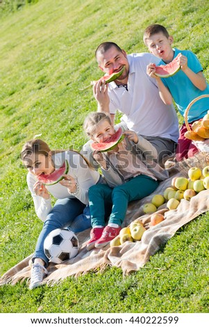 Joyful  young parents with two children enjoying watermelon on the picnic in sunny day - stock photo